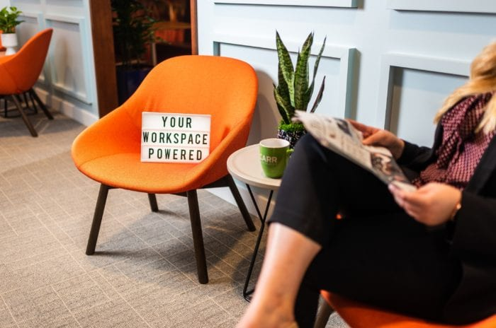 "Sign stating ""Your Workspace Powered"" placed on a bright, vibrant chair at a Carr Workplaces location."