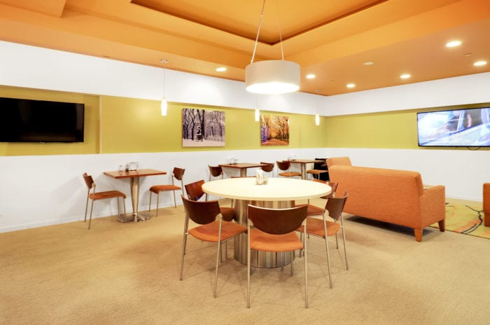Cafe area with array of seating and a TV at Carr Workplaces Central Park