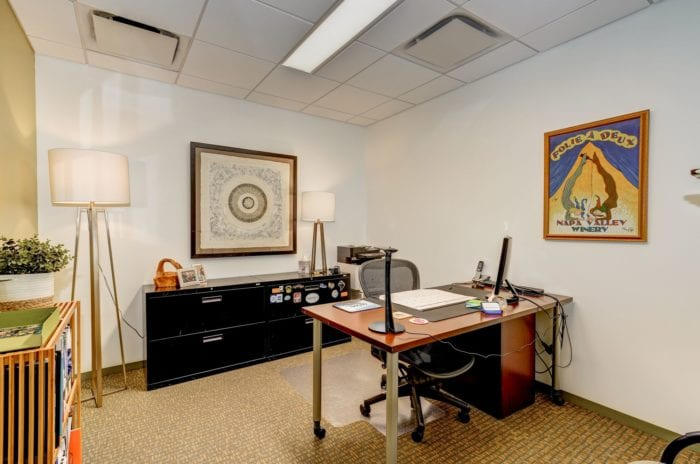 Private office space with vibrant, psychedelic style artwork.