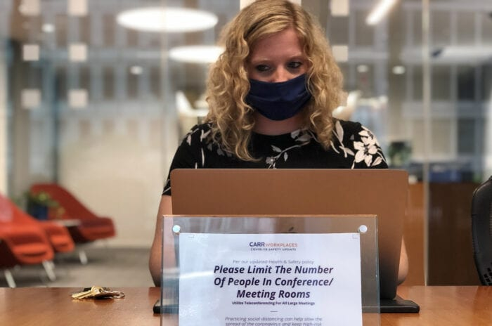 Mask-bearing woman sitting in a Carr Workplaces conference room rental