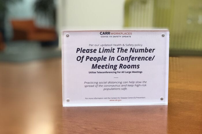 """Please Limit the Number of People in Conference & Meeting Rooms"" sign at Carr Workplaces"